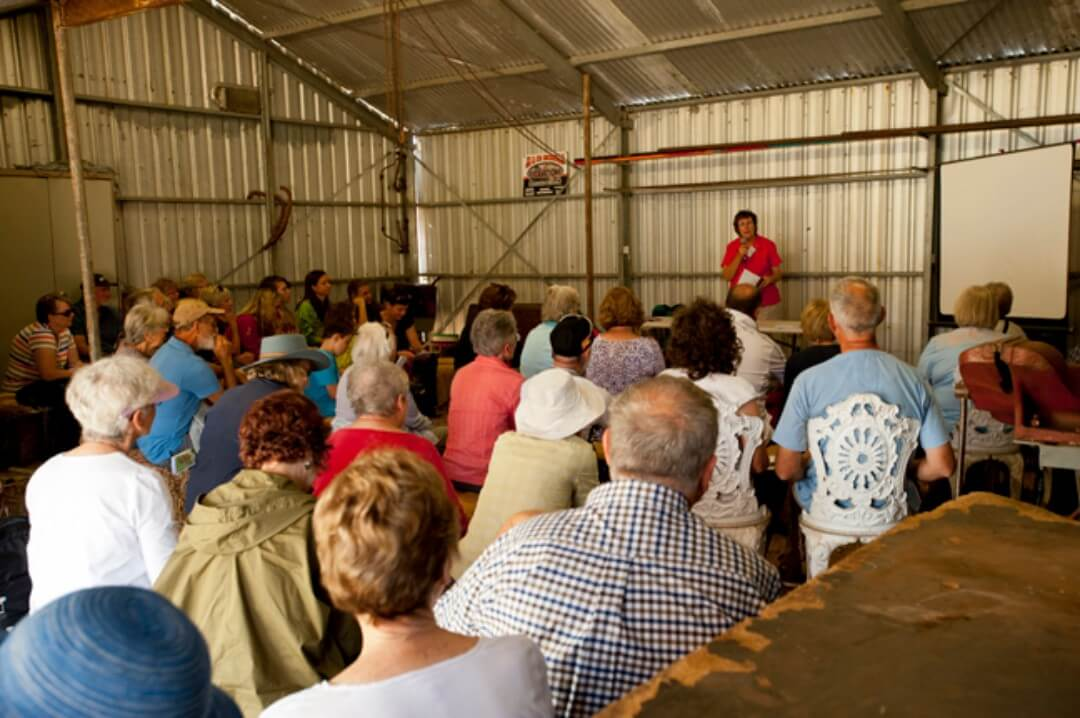 crowd in shed listening to bird speaker