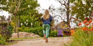 girl with blond hair running in garden